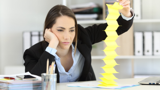 Woman playing with post it notes at desk looking bored