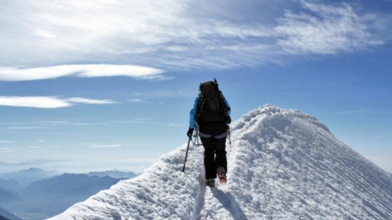 mountain climber walking up snomy mountain towards the summit