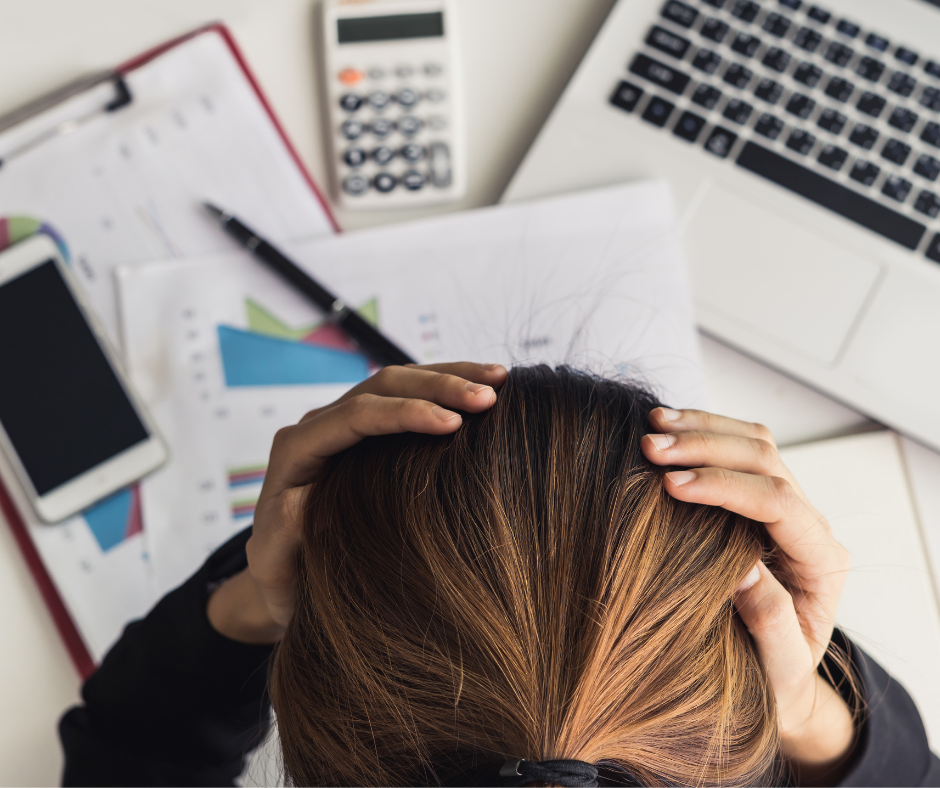 Woman holding her head at her desk
